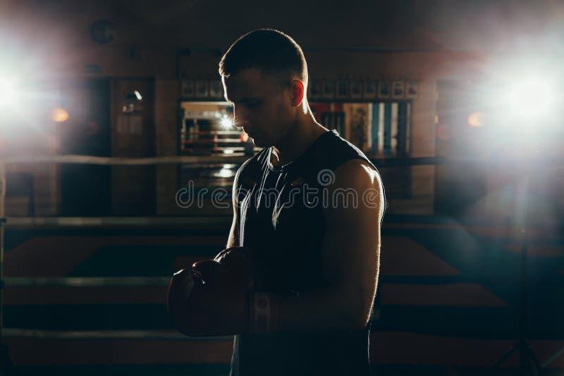Retrato de um homem novo muscular em luvas de encaixotamento no anel imagem de stock royalty free