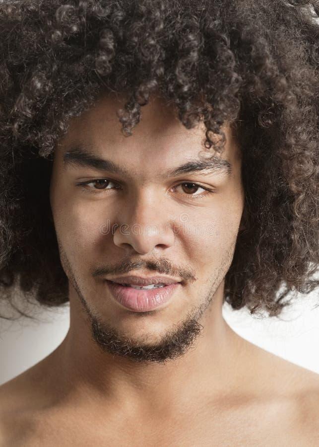 Retrato de um homem novo na moda com cabelo encaracolado sobre o fundo branco fotografia de stock