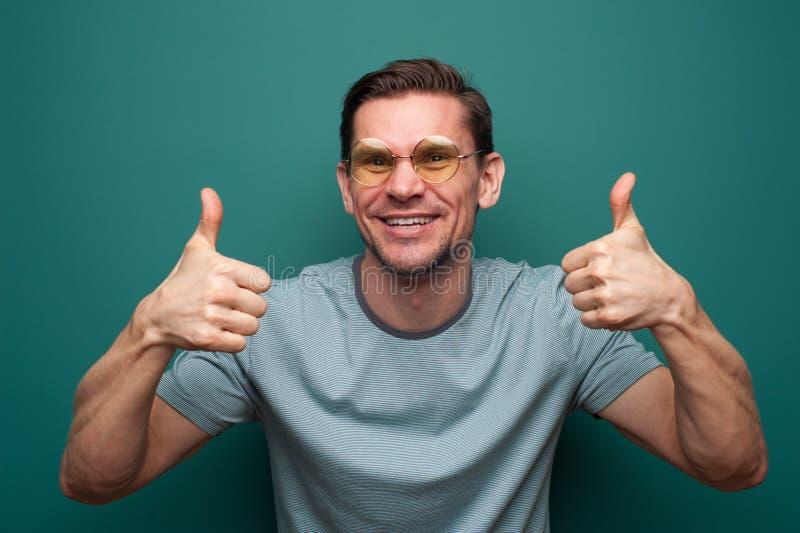 Retrato de um homem novo positivo nos vidros imagem de stock