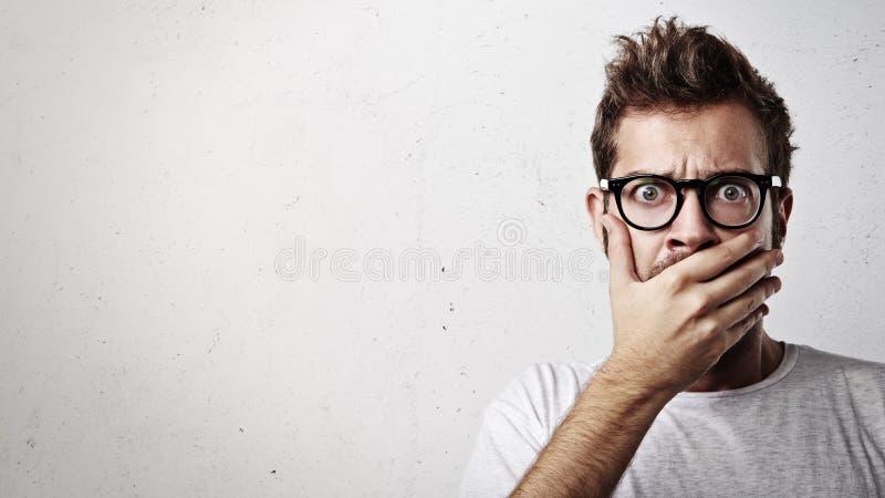 Retrato de um homem novo que cobre sua boca com a mão fotos de stock royalty free
