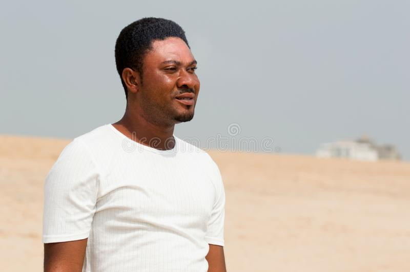 Retrato de um homem novo que está na praia foto de stock