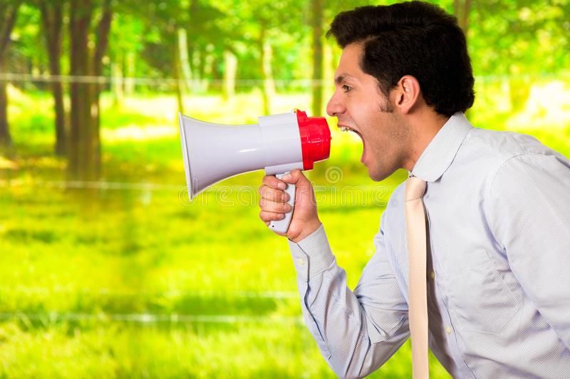 Retrato de um homem novo que grita com um megafone, em um fundo verde borrado fotografia de stock royalty free