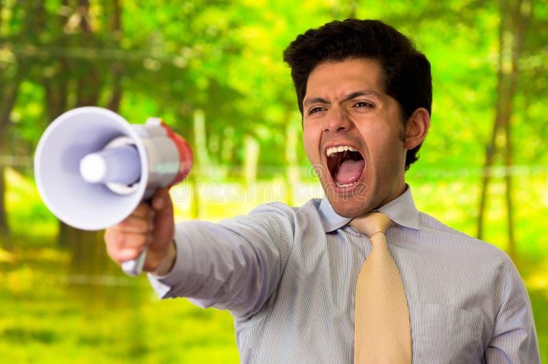 Retrato de um homem novo que grita com um megafone, em um fundo verde borrado imagem de stock
