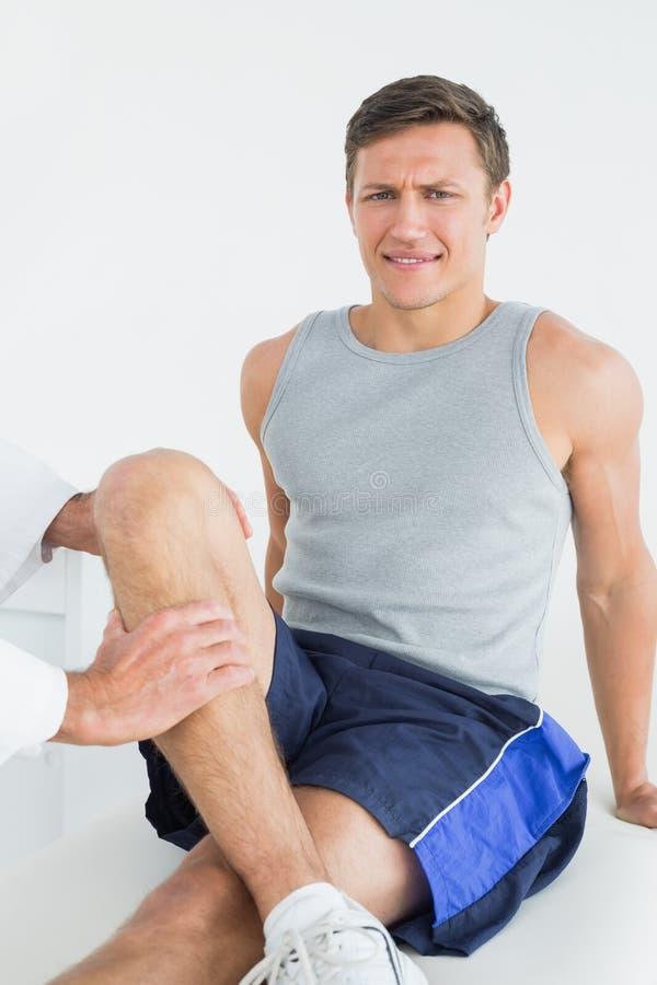 Retrato de um homem novo que obtém seu pé examinado fotos de stock