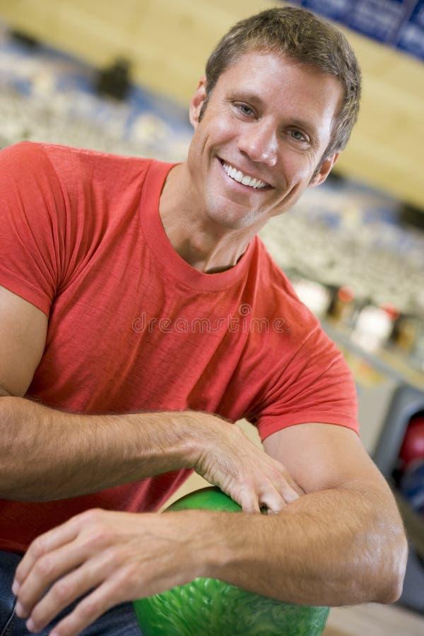 Retrato de um homem novo que prende uma esfera de bowling fotos de stock