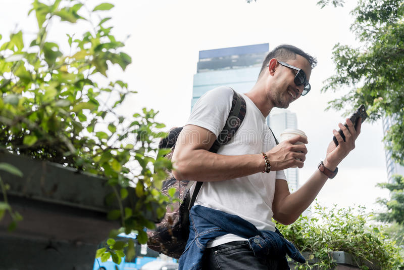 Retrato de um homem novo que sorri ao usar um durin do telefone celular fotos de stock