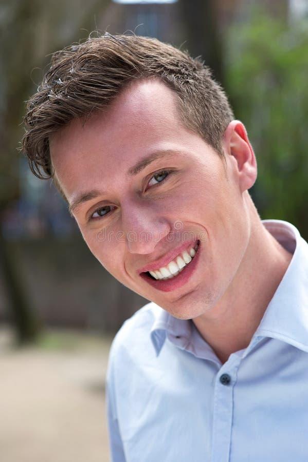 Retrato de um homem novo seguro que sorri fora foto de stock
