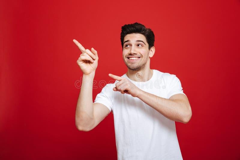 Retrato de um homem novo de sorriso em apontar branco do t-shirt fotos de stock