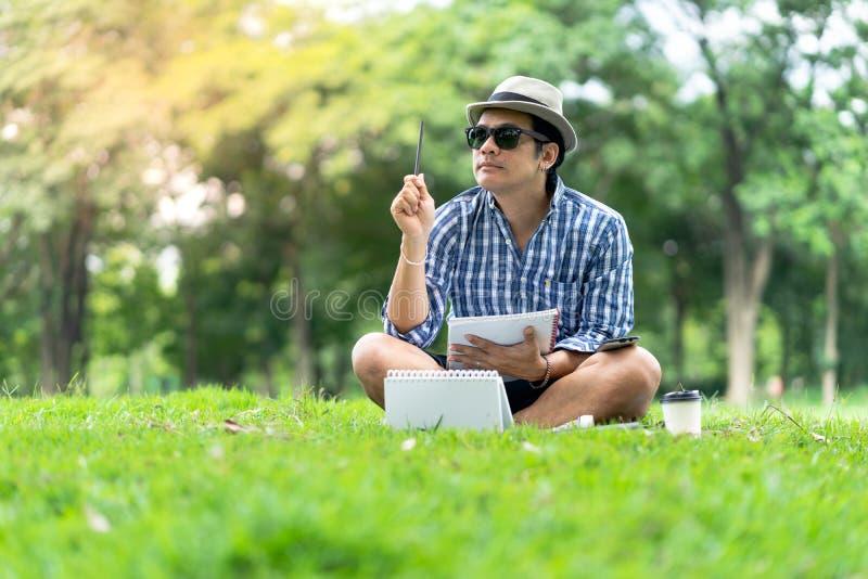 Retrato de um homem ocasional concentrado no chapéu que mantém o caderno foto de stock