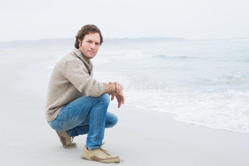 Retrato de um homem ocasional sério que relaxa na praia imagens de stock royalty free