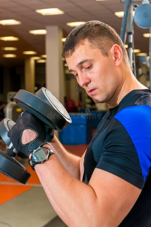 Retrato de um homem que exercita com pesos fotografia de stock royalty free