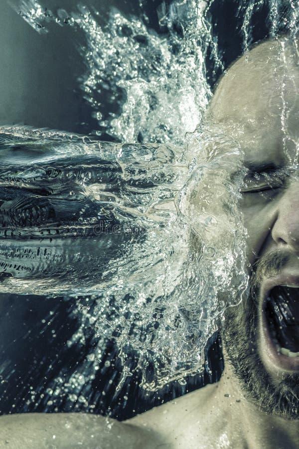 Retrato de um homem que recebe uma cubeta da água em sua cara imagem de stock royalty free