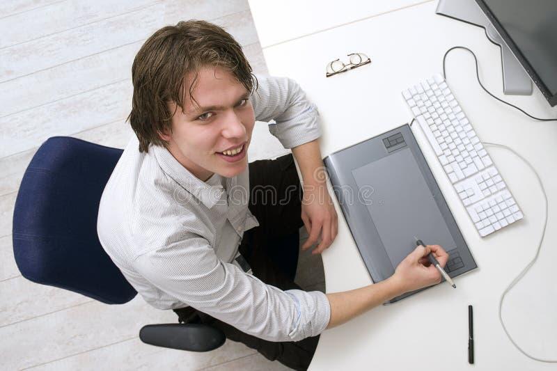 Retrato de um homem que senta-se atrás de uma mesa fotografia de stock royalty free