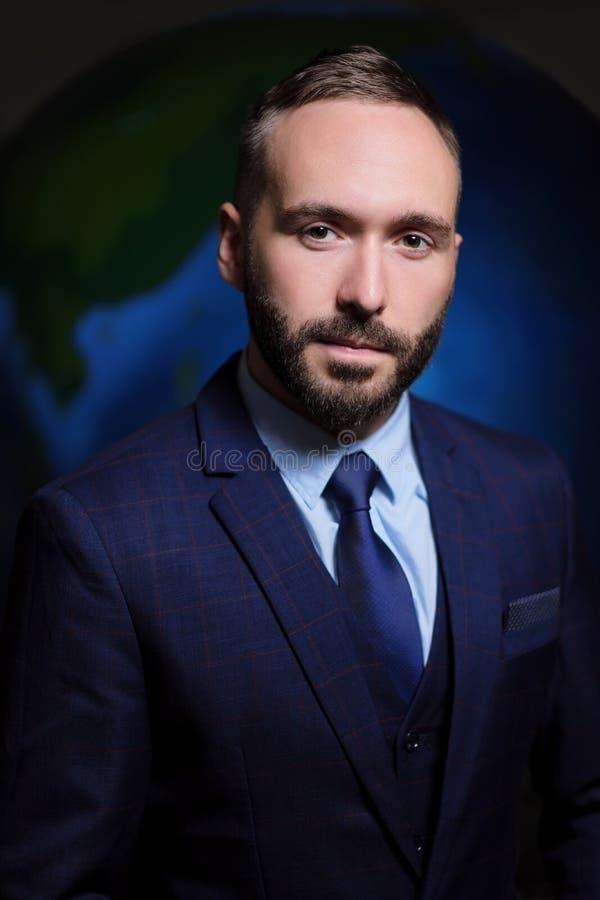 Retrato de um homem sério em um chefe do homem de negócios do terno e do laço em um fundo escuro da terra do globo fotos de stock royalty free