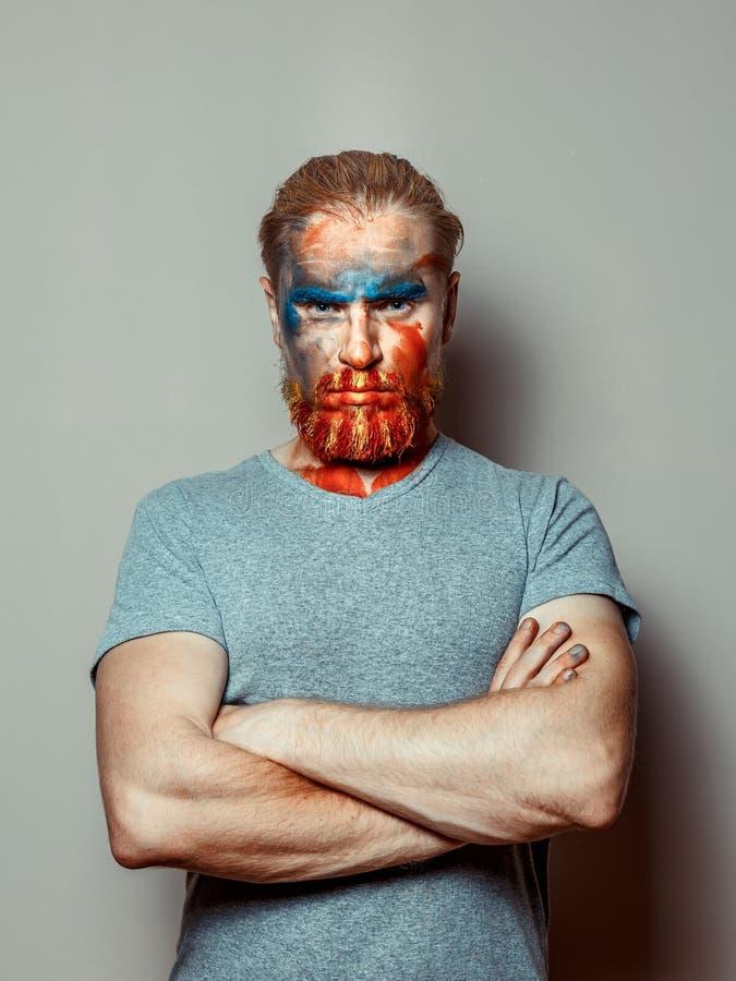 Retrato de um homem severo com uma barba e uma cara pintada, parte traseira do cinza imagens de stock