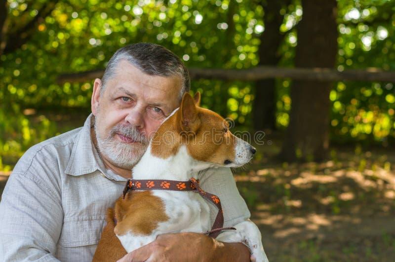 Retrato de um homem superior farpado com seu cão bonito fotografia de stock royalty free