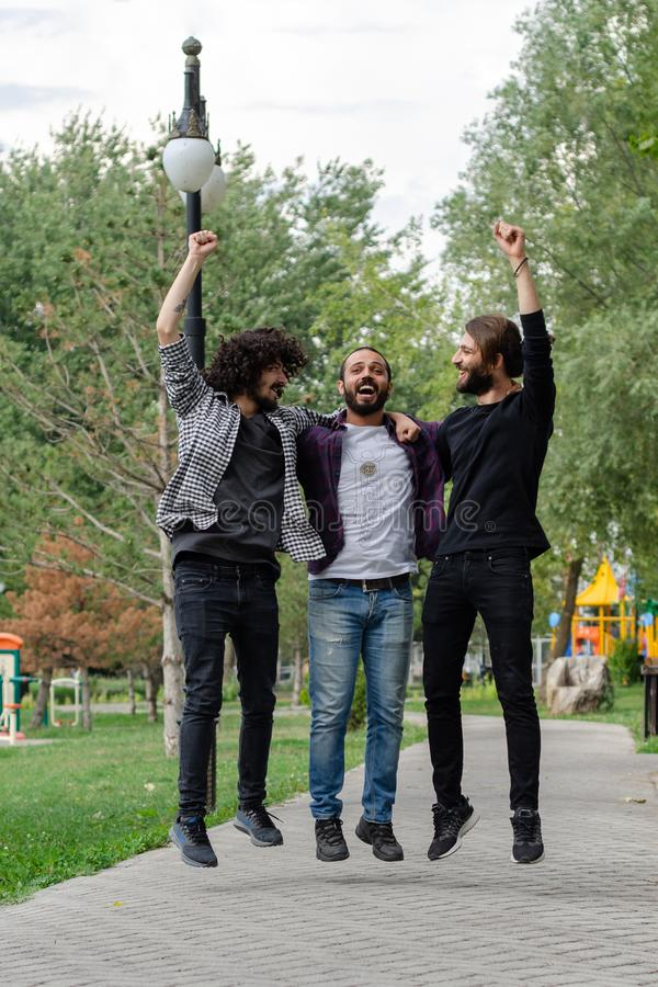 Retrato de um homem três novo alegre que salta e que comemora fotografia de stock