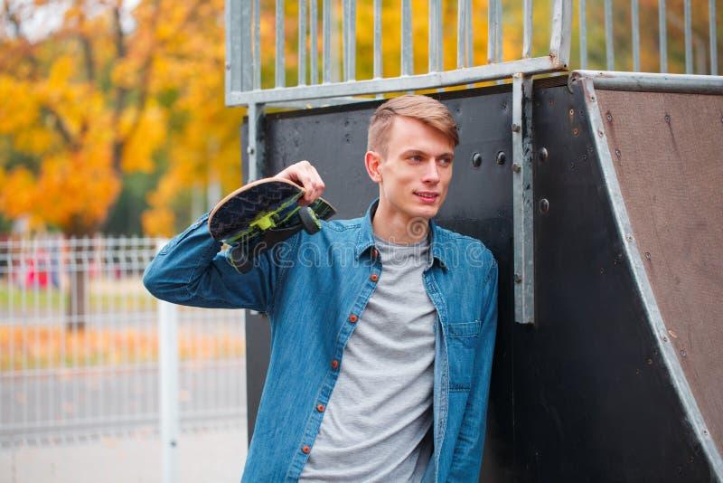 Retrato de um indivíduo considerável que está com um skate em suas mãos imagem de stock