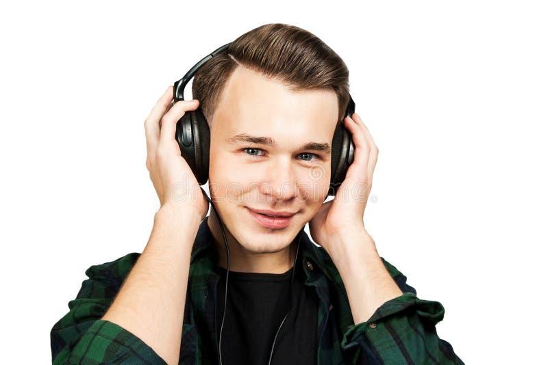 Retrato de um indivíduo novo branco caucasiano para escutar música nos fones de ouvido Homem considerável vestido em um t-shirt p fotografia de stock