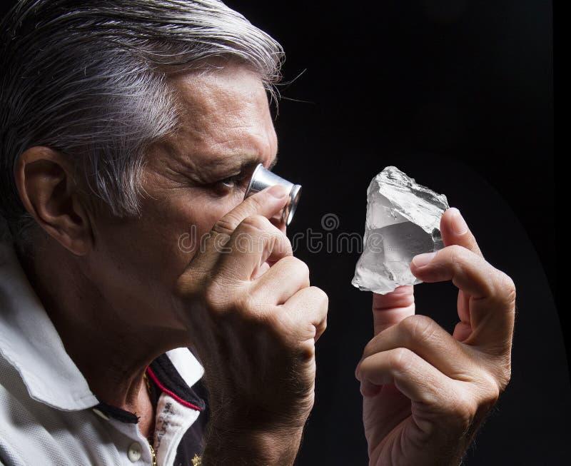 Retrato de um joalheiro durante a avaliação das joias imagem de stock