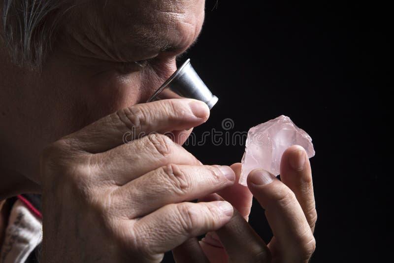 Retrato de um joalheiro durante a avaliação das joias fotos de stock