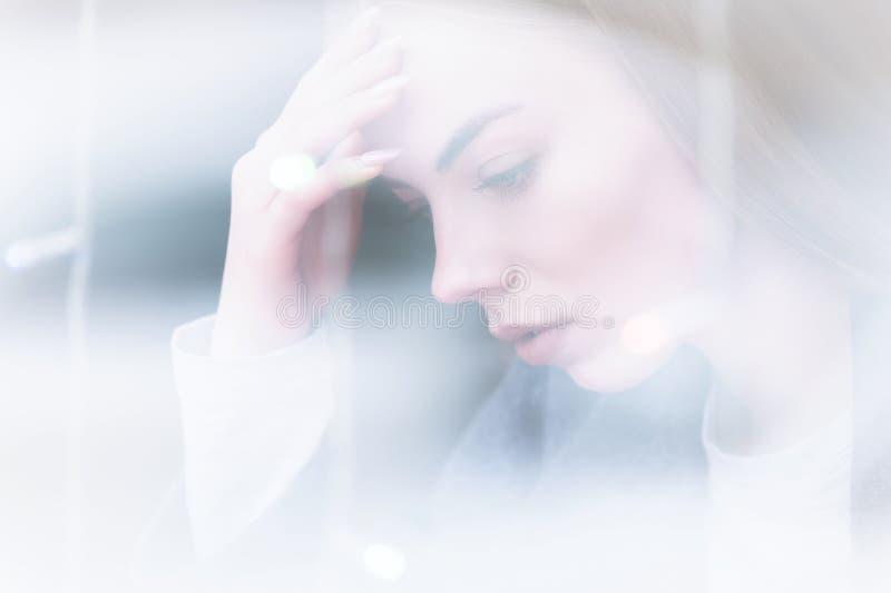 Retrato de um journalista fêmea novo atrativo que aferra-se a sua cabeça preocupada ou em uma dor de cabeça em um café atrás da fotografia de stock