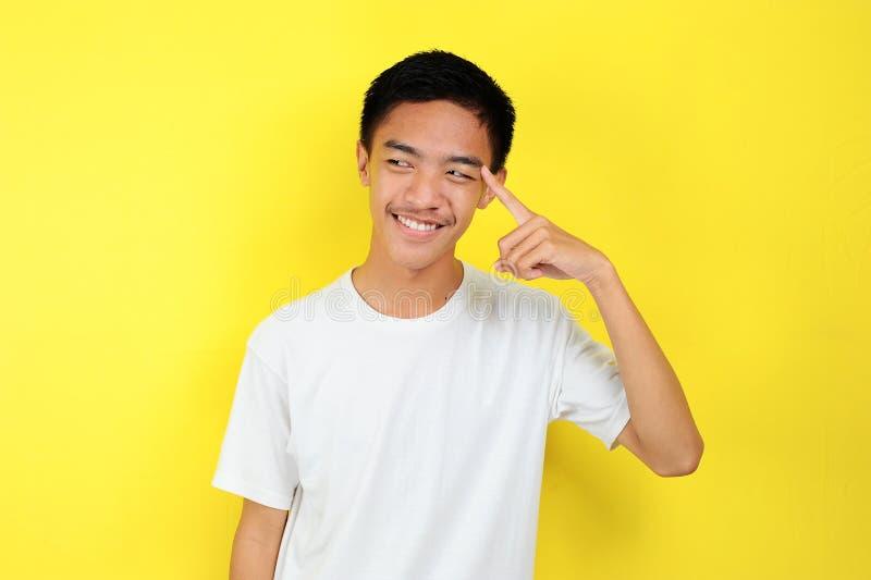 Retrato de um jovem asiático esperto a fazer gestos de pensamento Feliz jovem asiático a usar camiseta branca a pensar e a olhar  foto de stock royalty free