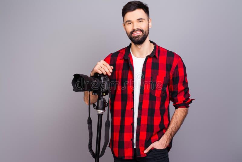 Retrato de um jovem cameraman bonito em estúdio com câmera imagem de stock