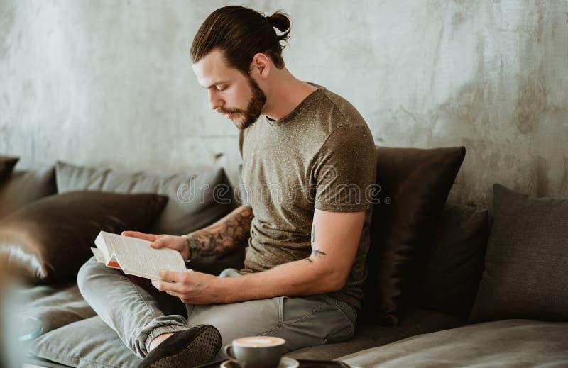 Retrato de um jovem hipster barbudo sentado no café enquanto lê livro e olha de lado fotografia de stock royalty free