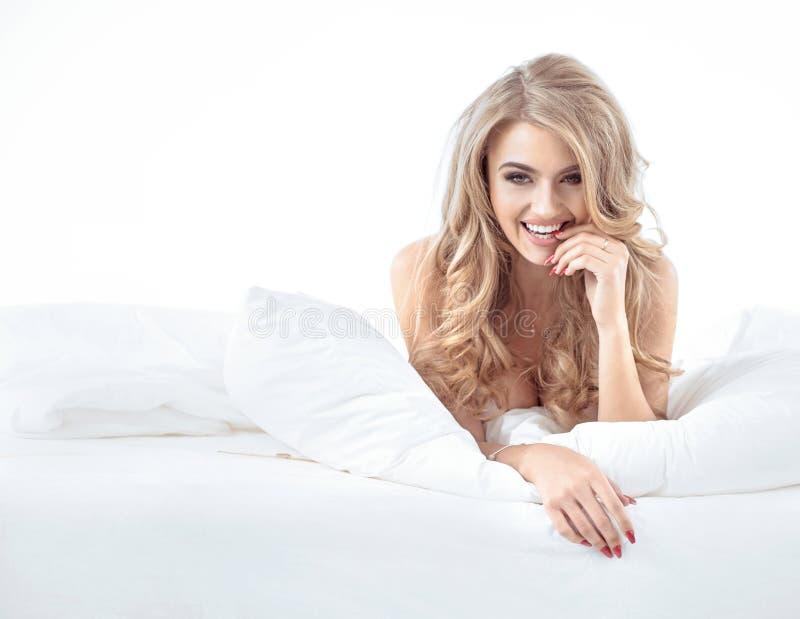 Retrato de um louro alegre que coloca na cama macia imagens de stock royalty free