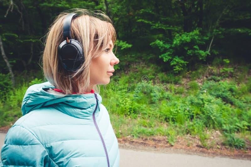 Retrato de um louro atrativo da menina dos esportes em uma luz que corre abaixo dos fones de ouvido do bluetooth do molho do reve fotografia de stock