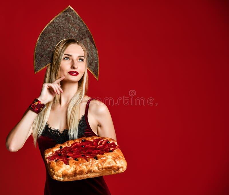 Retrato de um louro bonito novo que guarda uma torta caseiro deliciosa da cereja imagens de stock