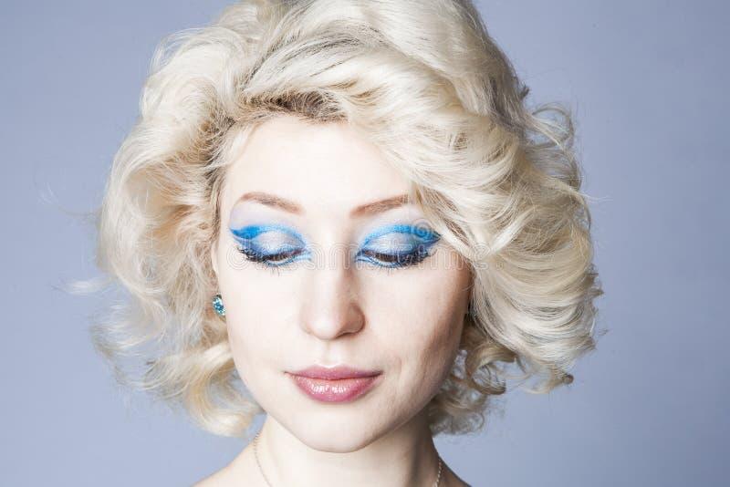 Retrato de um louro novo em um vestido azul com composição dos olhos azuis imagens de stock royalty free