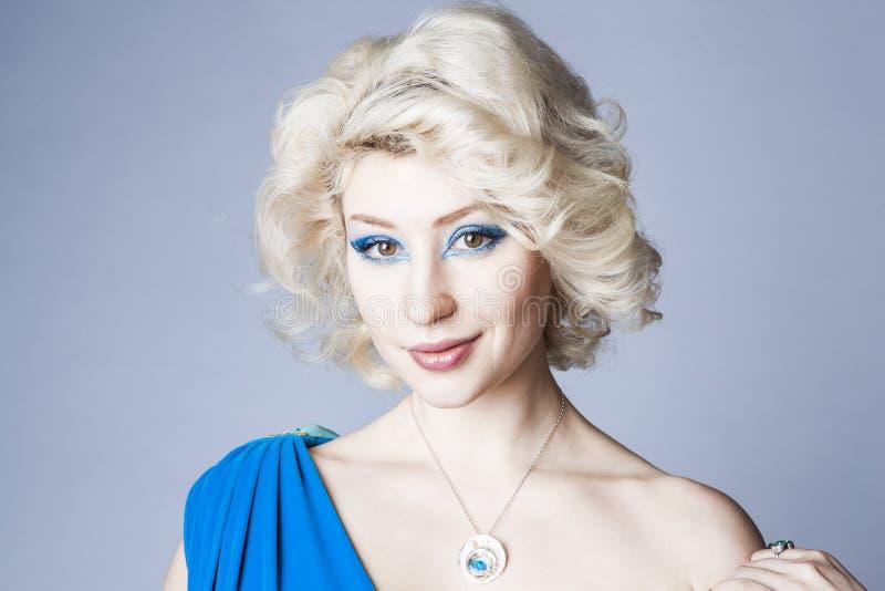 Retrato de um louro novo em um vestido azul com composição dos olhos azuis foto de stock royalty free