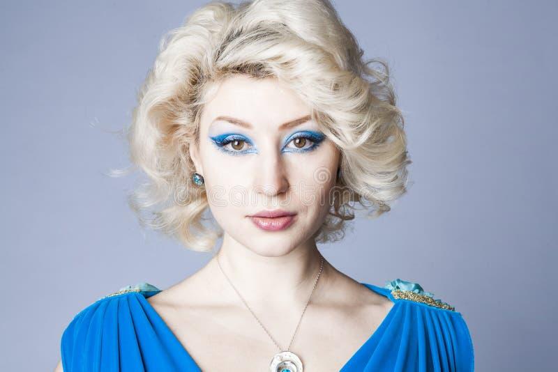 Retrato de um louro novo em um vestido azul com composição dos olhos azuis fotografia de stock royalty free