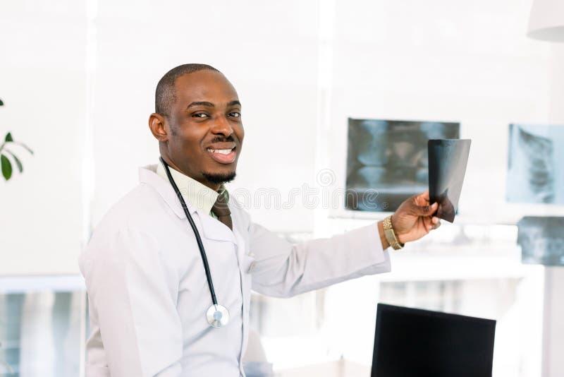 Retrato de um médico olhando para uma radiografia Homem de sangue negro afro-americano no hospital foto de stock royalty free