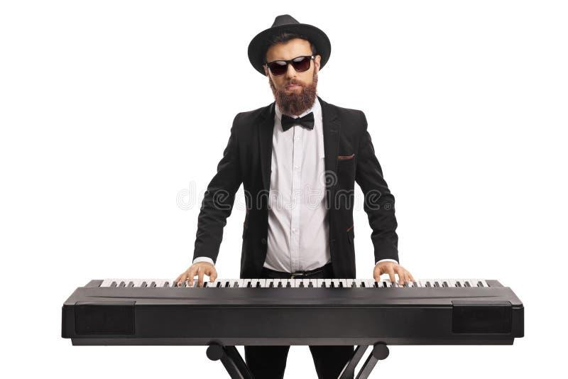 Retrato de um músico masculino em um terno que joga um teclado foto de stock royalty free