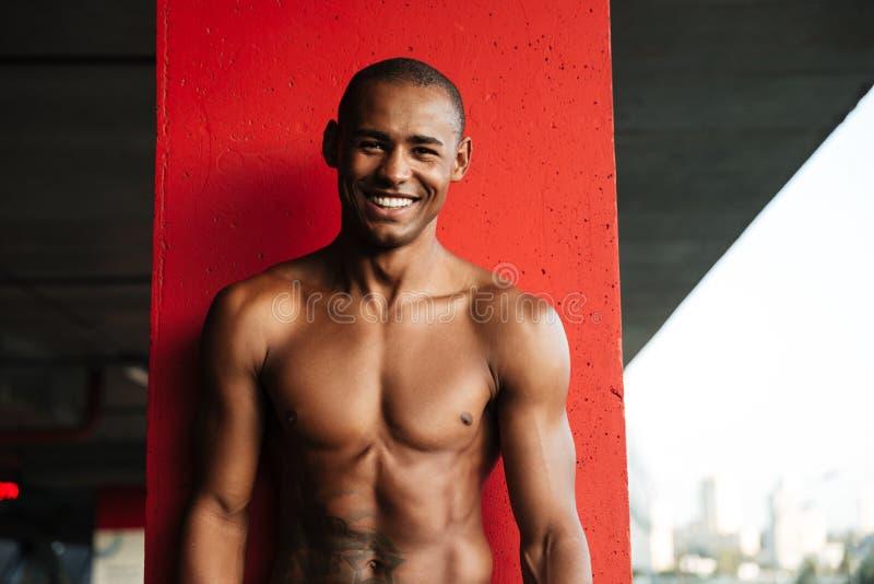 Retrato de um meio desportista africano despido de sorriso atrativo foto de stock