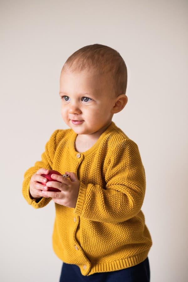 Retrato de um menino bonito da criança que guarda uma bola vermelha fotografia de stock