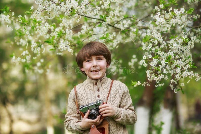 Retrato de um menino bonito de sorriso que toma a imagem com câmera retro imagens de stock royalty free