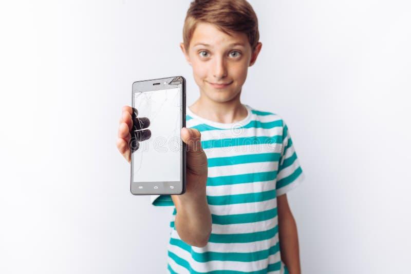 Retrato de um menino bonito e emocional, cujas nas mãos um telefone quebrado mostra a surpresa, fundo branco, de um t-shirt azul, imagens de stock