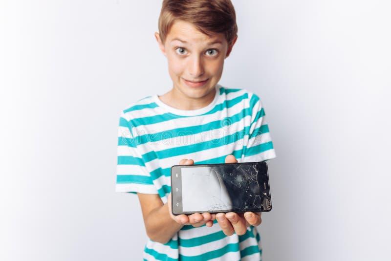 Retrato de um menino bonito e emocional, cujas nas mãos um telefone quebrado mostra a surpresa, fundo branco, de um t-shirt azul, imagem de stock royalty free
