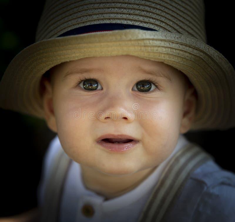 Retrato de um menino com um chapéu quebrado foto de stock