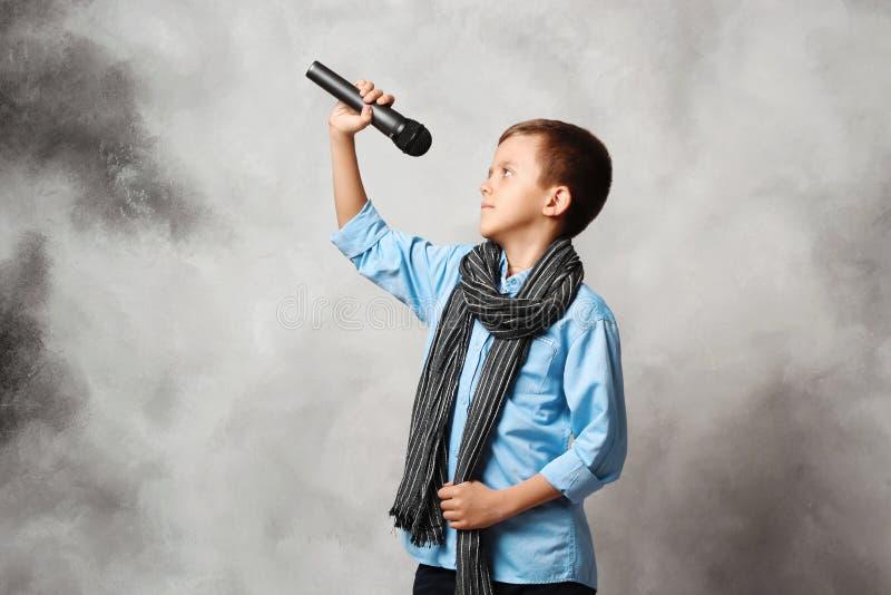 Retrato de um menino com um microfone fotos de stock royalty free