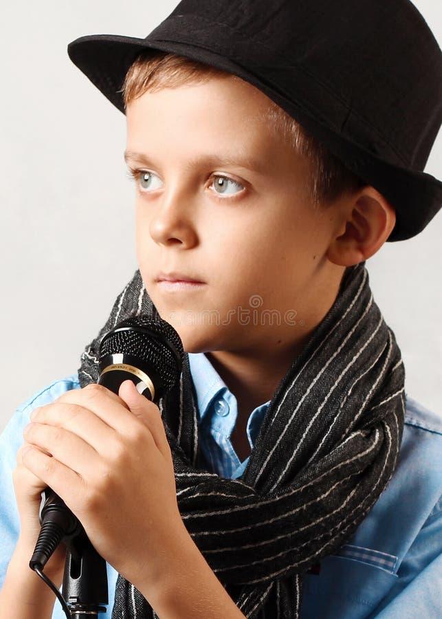 Retrato de um menino com um microfone fotos de stock