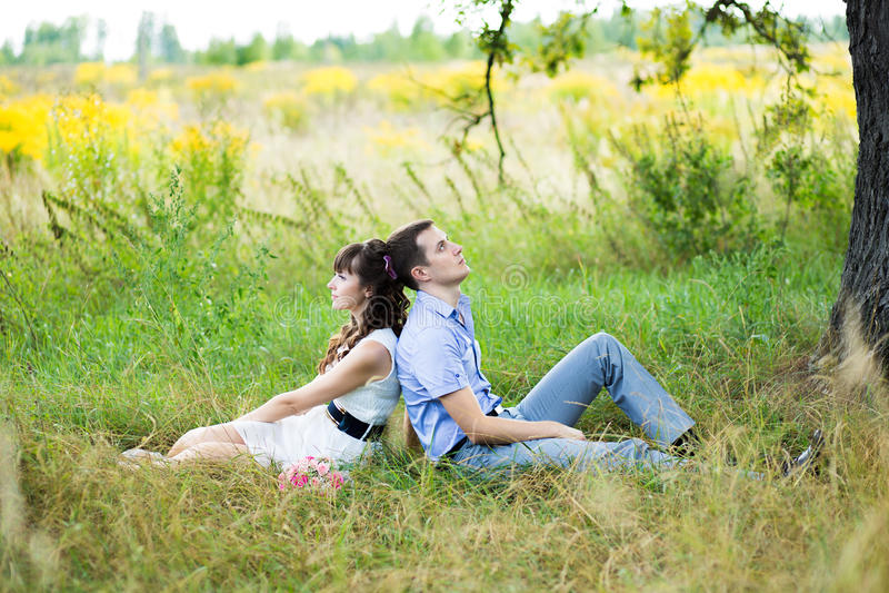 Retrato de um menino e de uma menina que sentam-se na grama imagens de stock royalty free