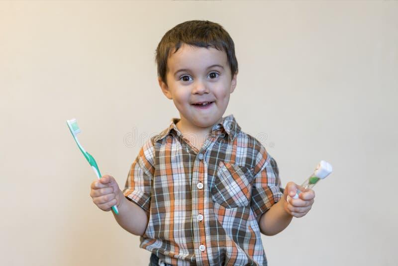 retrato de um menino louro caucasiano bonito bonito com uma escova de dentes Dentes de escovadela do rapaz pequeno e sorriso ao t imagens de stock royalty free