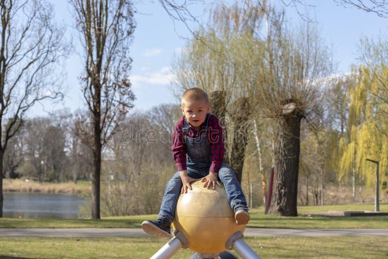 Retrato de um menino louro do litte no campo de jogos foto de stock