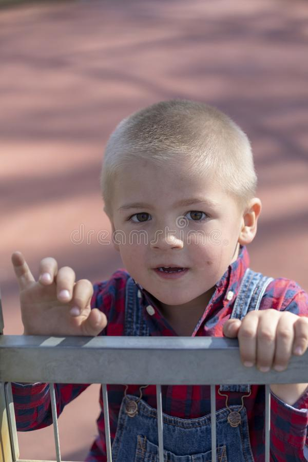 Retrato de um menino louro do litte no campo de jogos imagem de stock