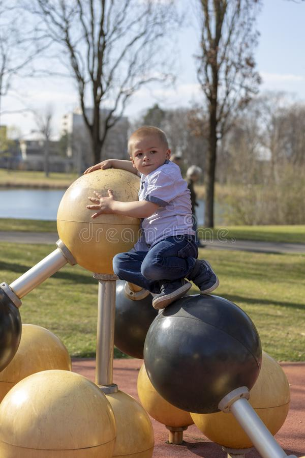 Retrato de um menino louro pequeno no campo de jogos imagem de stock royalty free